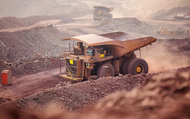 Kuorma-auto nostaa pölyä ilmaan kaivosalueella